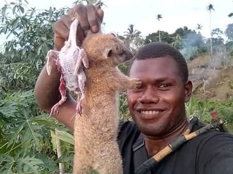 A man holding up a Cuscus, similar to possum